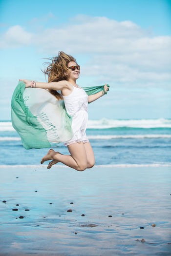 Woman Holding Shawl While Jumping On Shore At Beach
