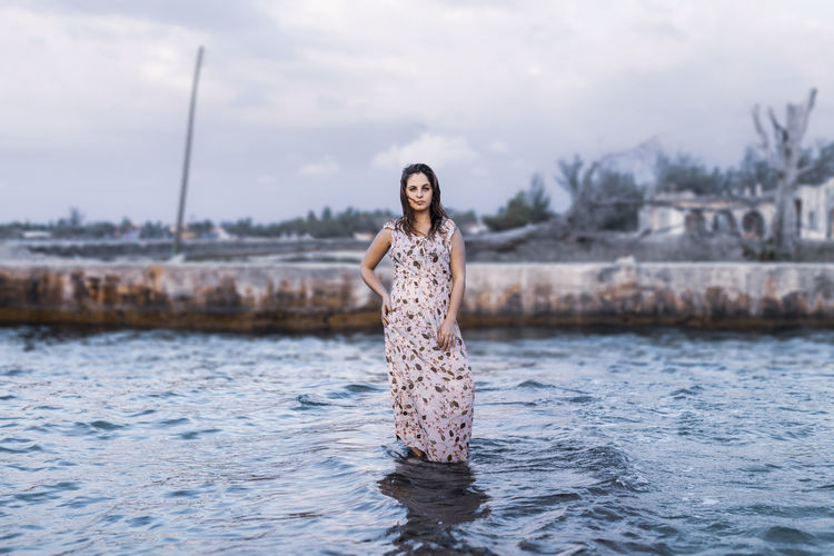 Portrait of young woman standing in sea against sky