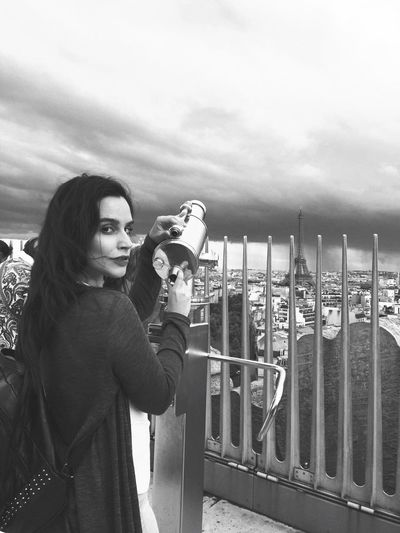 Portrait of young woman holding hand-held telescope against cityscape