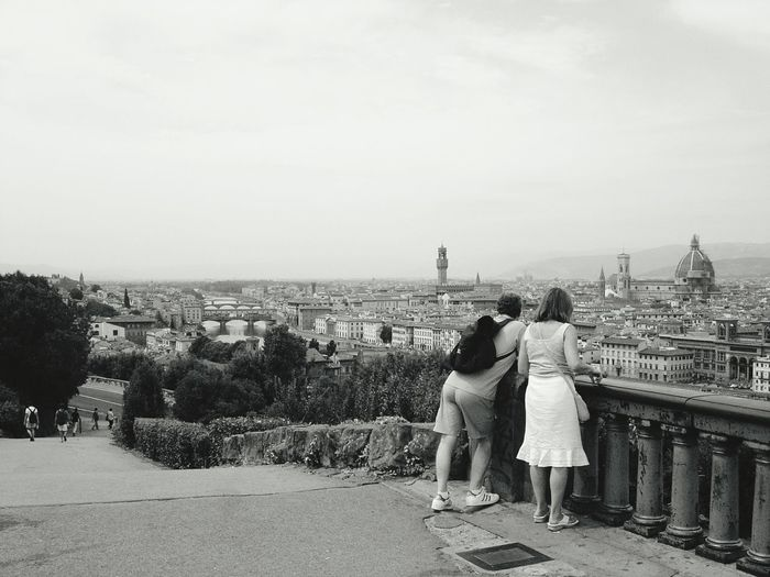 Rear View Of Tourists Looking At View Of City