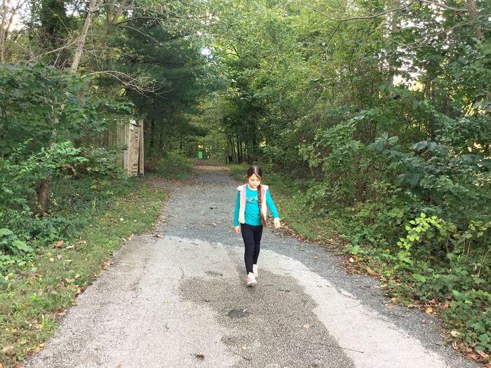 Full length of girl walking on road amidst trees