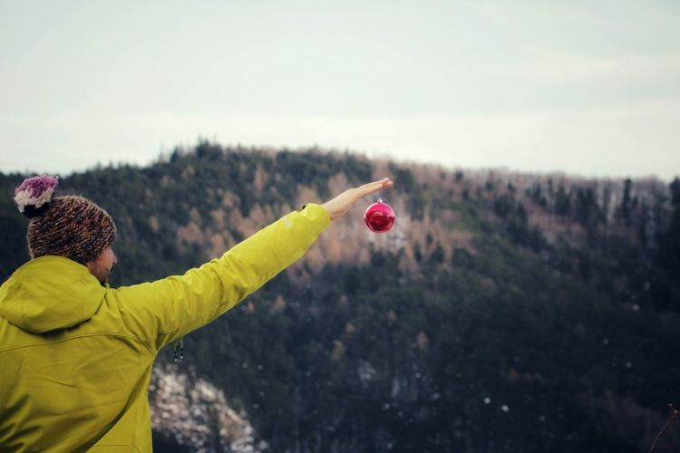 Rear View Of Man Holding Bauble Against Mountain
