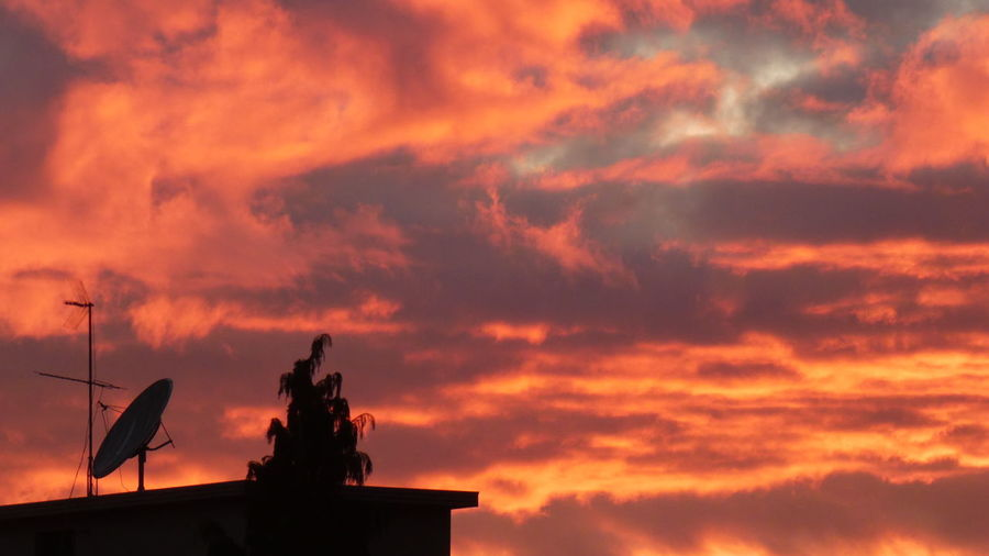 Low angle view of silhouette statue against orange sky