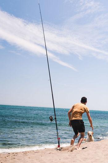 Rear view of men on beach against sky