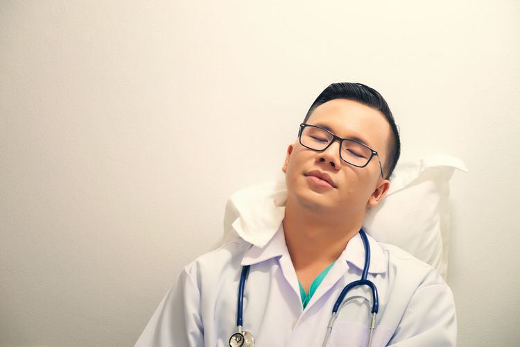 Tired Doctor Sleeping While Sitting On Chair At Hospital