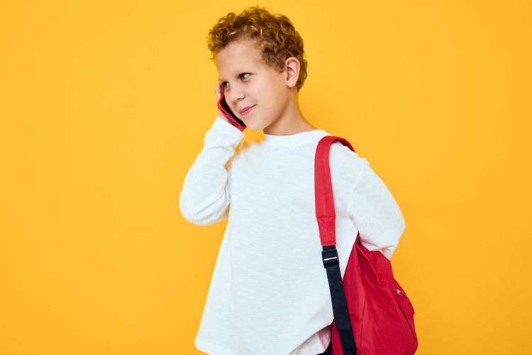 Boy holding yellow while standing against orange background