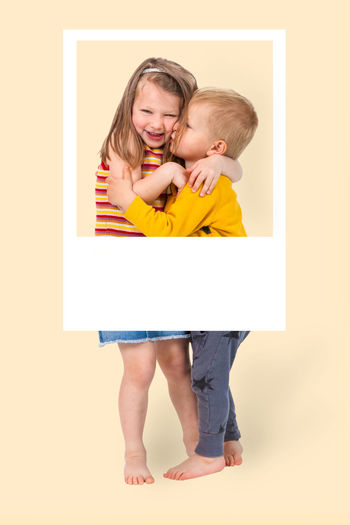 portrait of two little brothers hugging each other and exchanging affection. stylish white frame can be used to add text. Happy Love Family Brothers Brother Sister Child Children Color Kiss Kisses Affectionate Feelings Like Togetherness Warmth Attachment Relationship Childhood Smile Smiling Happyness Caucasian Females Males  Caring Two People People Portrait Studio Shot Friendship Fondness Hug Embrace Frame Polaroid Framed Including Concept Happiness Together Fun Beauty Backgrounds Yellow Full Length Indoors  Emotion Front View Standing Bonding Innocence Positive Emotion