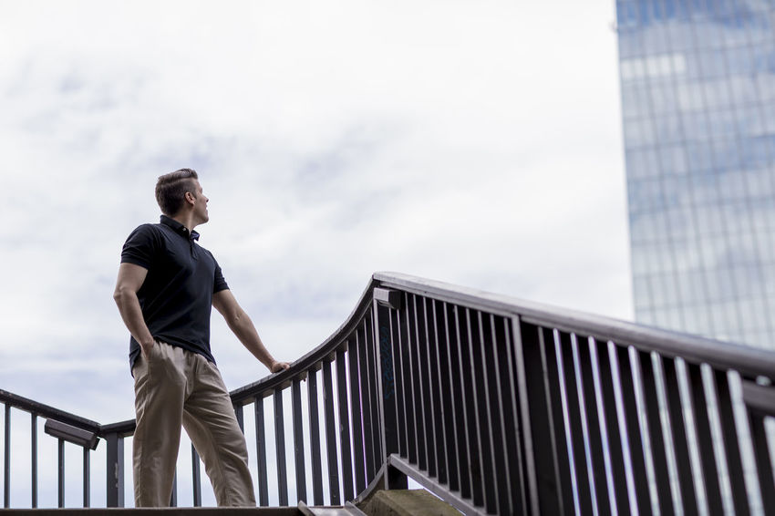 Handsome man dressed casually standing in an outdoor stairwell with one hand in his pocket and looking towards a skyscraper. Adult Architecture Balustrade Cloudy Khaki Pants Long Shot Man Stairs Standing Casual Clothing Caucasian Day Golf Shirt Good Looking Hand In Pocket Handrail  Handsome Looking Away From Camera Low Angle Office Building Outside Sky Skyscraper Stairwell Summer