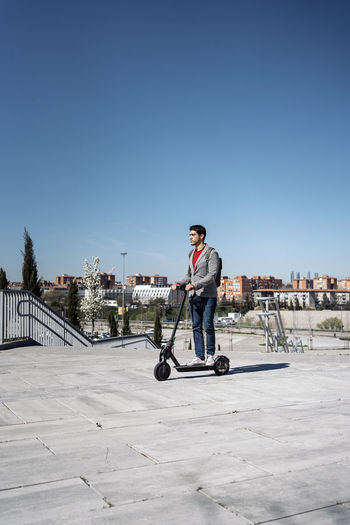 Man riding electric scooter on footpath