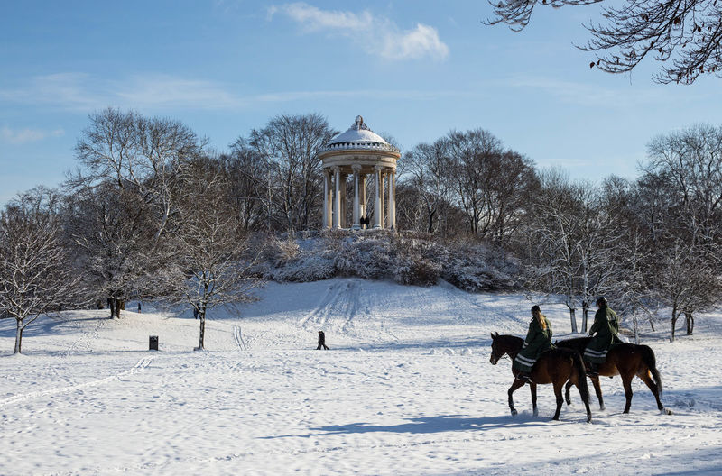 People riding a horse on snow covered landscape against sky