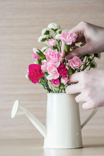 Close-up of hand holding bouquet of pink flower vase on table