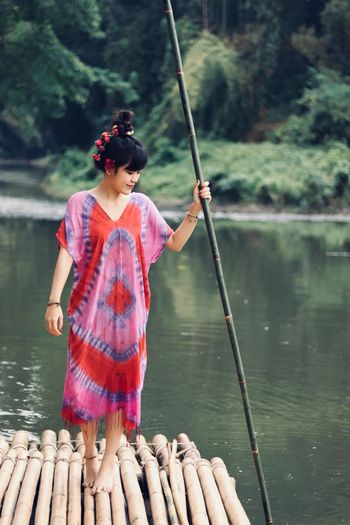 Woman holding bamboo while standing on wooden raft in lake