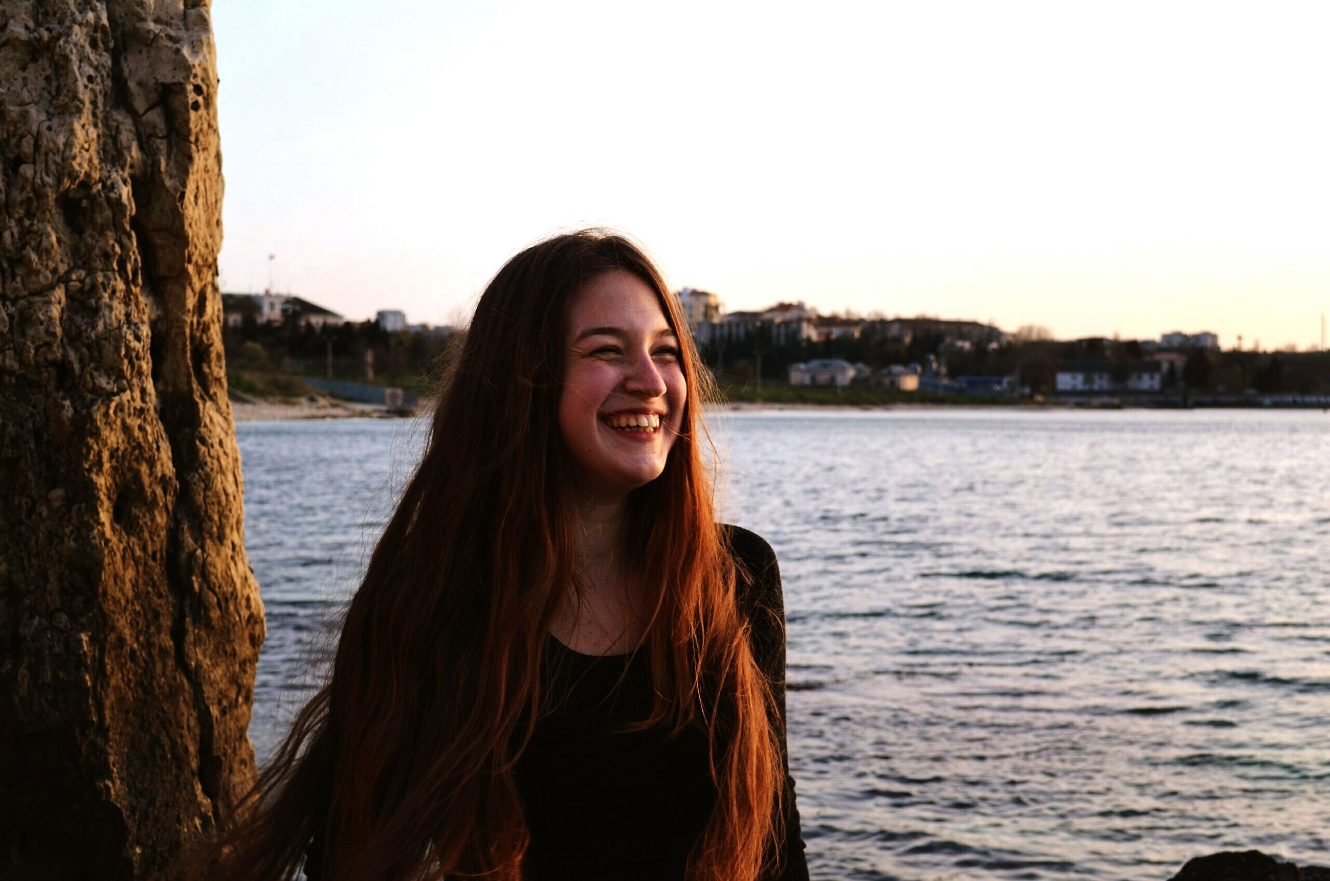young adult, looking at camera, portrait, young women, long hair, person, water, lifestyles, front view, smiling, standing, leisure activity, clear sky, waist up, casual clothing, focus on foreground, sea
