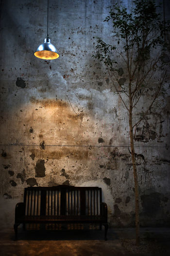 Illuminated Lamp Hanging Over Empty Bench Against Weathered Wall At Night