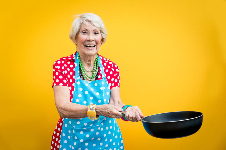 Portrait of smiling senior woman holding cooking pan against yellow background
