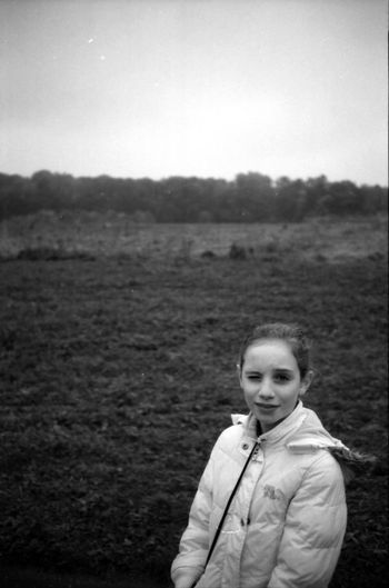 Portrait Of Teenage Girl Winking Eyes While Standing On Grassy Field During Winter
