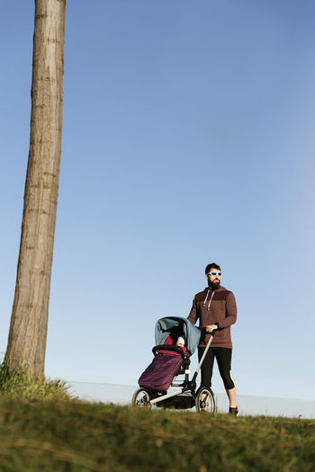 Man walking with baby stroller on field against sky