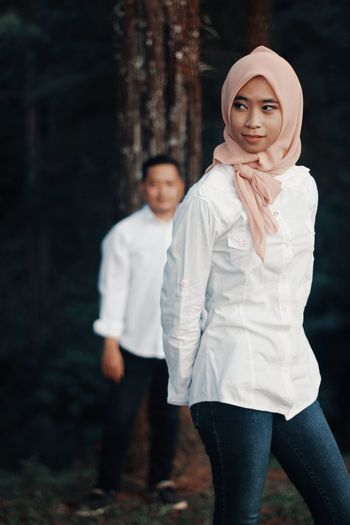 Woman in hijab walking with man at forest