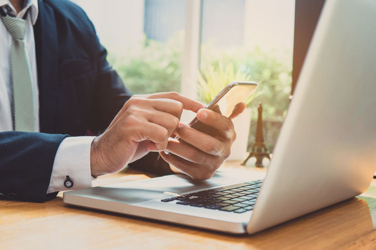 Midsection of businessman using phone by laptop on table