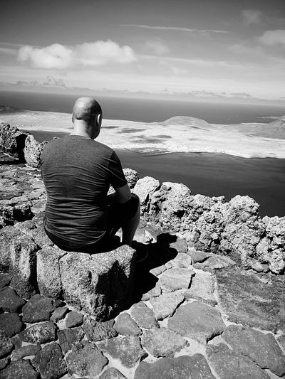 Contemplation From Behind Contemplation. Monochrome Thoughtful Males  Male Island Canary Islands Mirador Del Río High Sad Emotion Emotional Photography Sea Water Beach Sitting Men Sand Coastline Calm Rocky Coastline Headland Tranquil Scene Shore Horizon Over Water