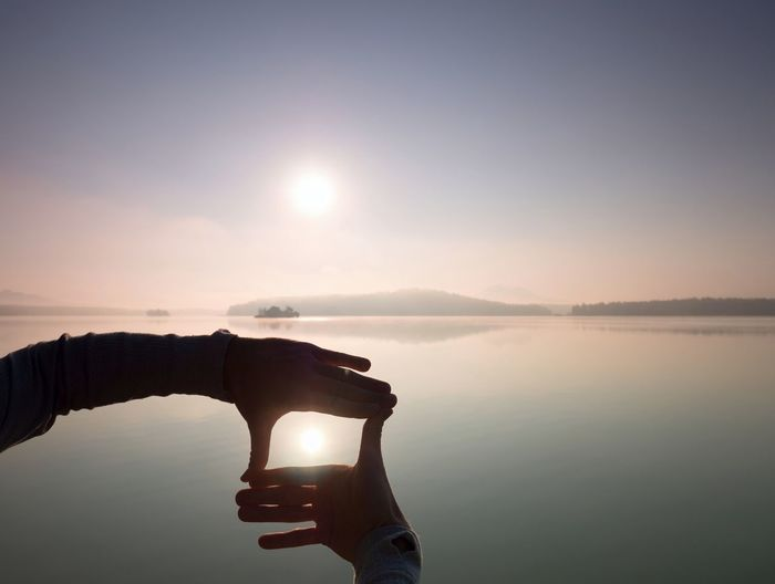 Reflection of hand holding water in lake against sky during sunset