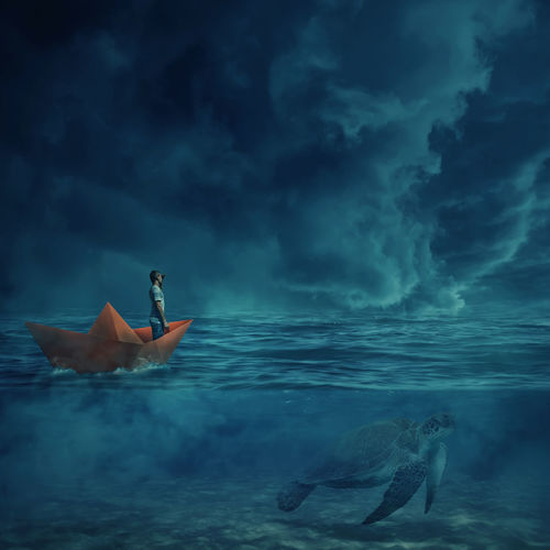 Digital composite image of man standing in paper boat on sea against sky at dusk