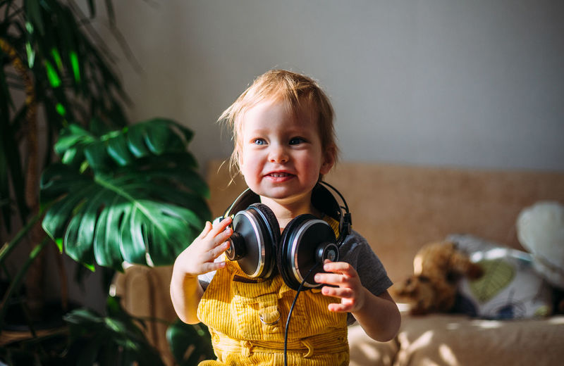 Funny little child having fun with headphones at home, portrait.