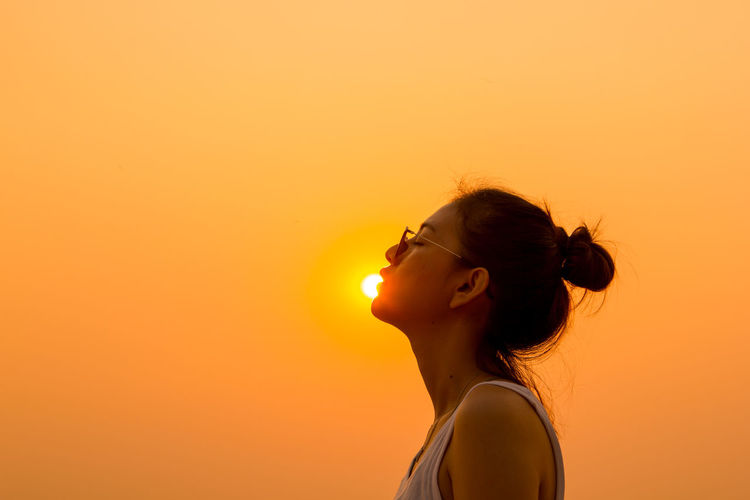 Optical illusion of young woman kissing sun against clear orange sky