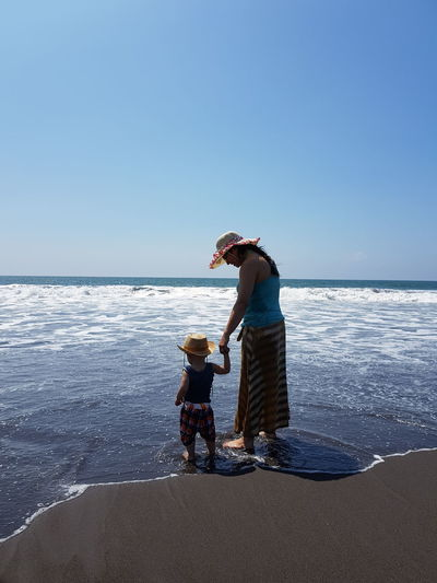 Mother and son standing on shore against blue sky