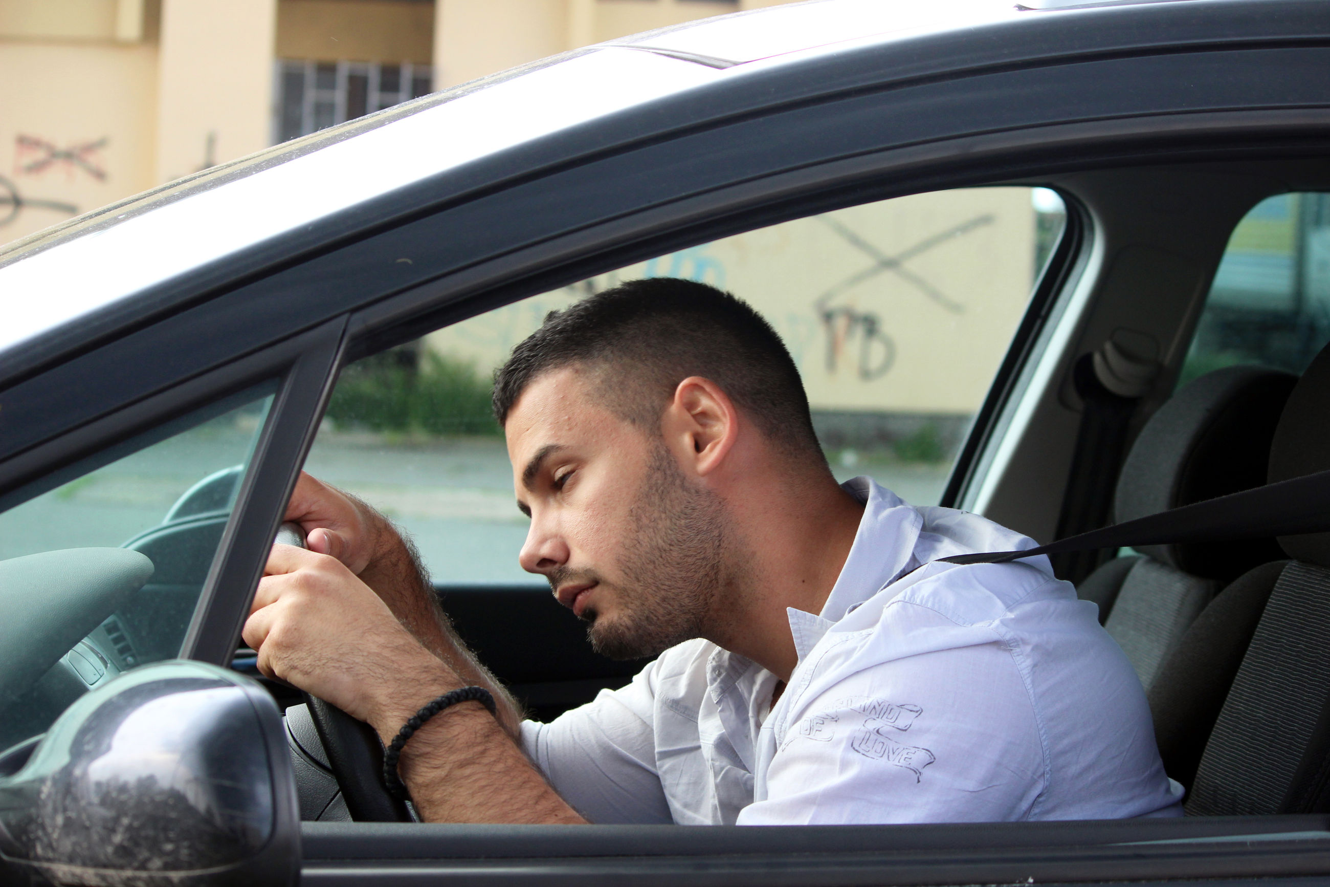 PORTRAIT OF A YOUNG MAN SITTING IN CAR