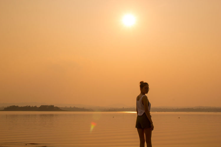 Woman standing in sea against sky during sunset