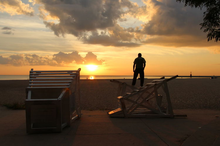 Rear view of silhouette man standing on fallen lifeguard chair at beach during sunset
