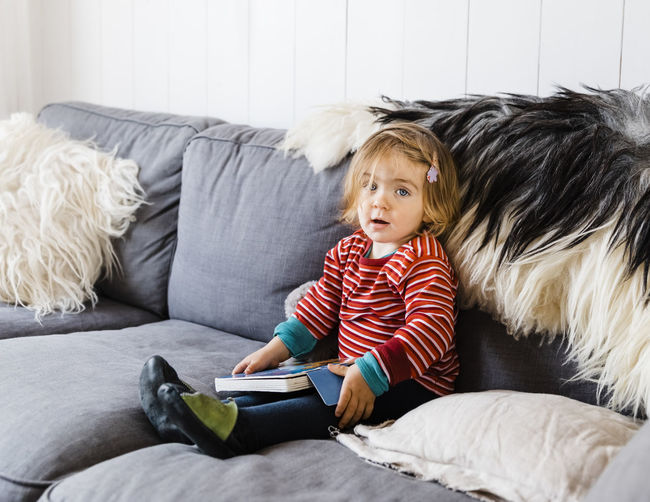 Portrait Of Girl Holding Book While Sitting On Sofa At Home