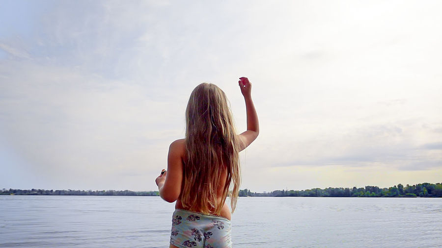 Shirtless Girl Standing At Lakeshore Against Sky