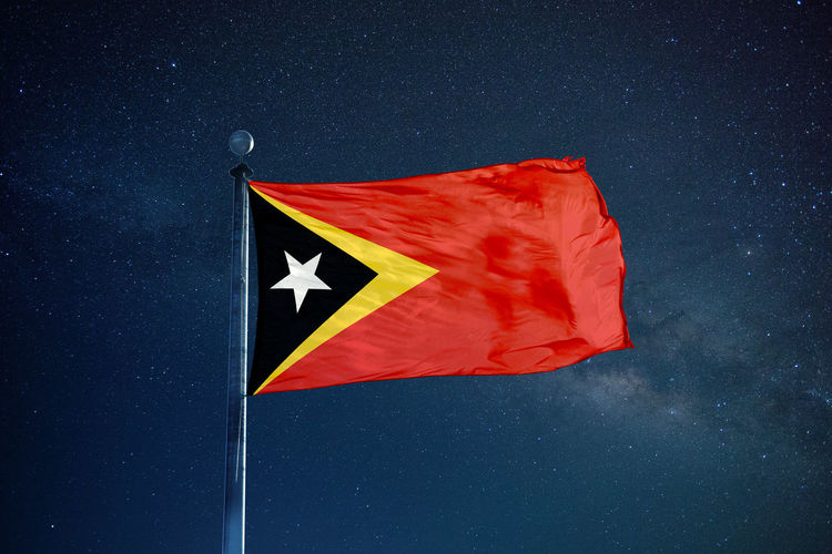 Low angle view of east timor flag against star field sky