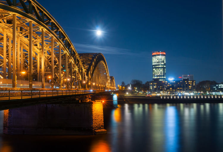 View of the Hohenzollernbridge, the Cologne Triangle, the Hyatt Regency and a beautiful bright Full Moon over the River Rhine at Night - in Germany Cologne 2018. Rhine Full Moon Moon Light Hohenzollernbridge Hohenzollernbrücke Water City Reflection Sky Bridge Connection Building Exterior Illuminated Night Germany River Blue Sky City Lights Architecture Built Structure Waterfront Travel Destinations Bridge - Man Made Structure Building No People Nature Office Building Exterior Skyscraper Outdoors Cityscape