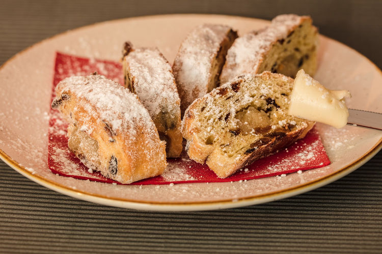 Stollen with powdered sugar and butter Easter Bread Snack Bread Butterfly Christmas Bread Filling Food Plate Of Food Powdered Sugar Rich Bread Seasons Greetings Stoll Sweet Bread