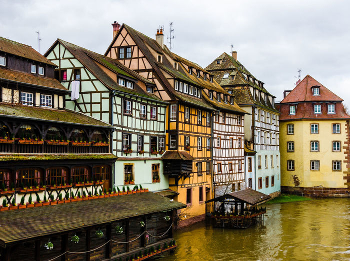 Half-timbered houses by canal in city against sky