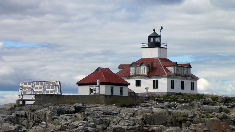 Architecture Birds Building Exterior Built Structure Cloud Cloud - Sky Coastline Day Harsh Lighthouse Maine Nature Navigation New England  No People Ominous Outdoors Red Roofs Remote Rock Sky Solar Power Weathered