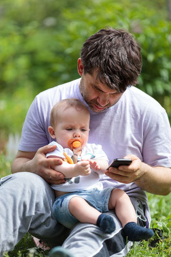 Baby Boy Cell Child Dad Family Father Grass Lap Little Park Phone Sit Smartphone SMS Text