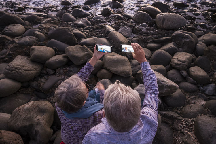 High Angle View Of Couple Taking Selfie From Mobile Phones On Rock At Beach
