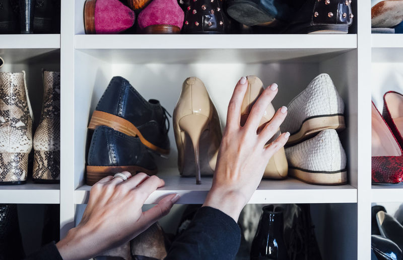 Low section of woman wearing shoes at store
