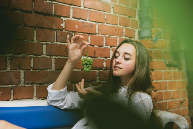 Smiling woman holding grapes while sitting by brick wall