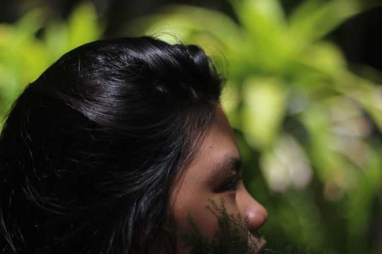 Cropped image of young woman looking away at park