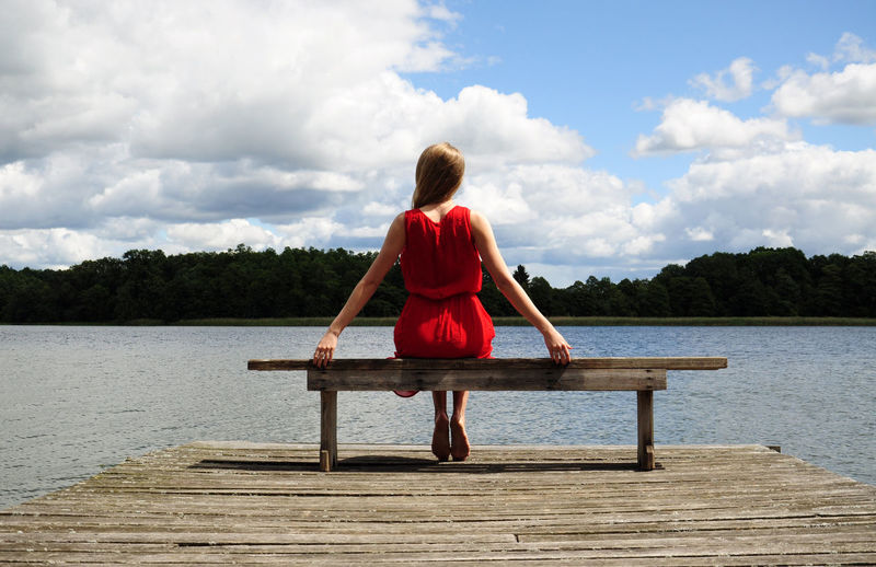Rear view of woman wearing red dress sitting on bench at jetty over lake against sky