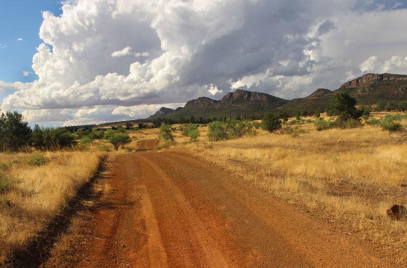Dirt road amidst landscape against sky, flinders rangers australia