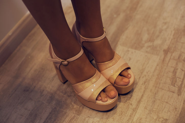 Low section of woman wearing shoes on hardwood floor
