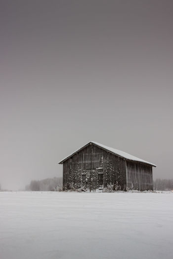 Snow covered barn by field against clear sky