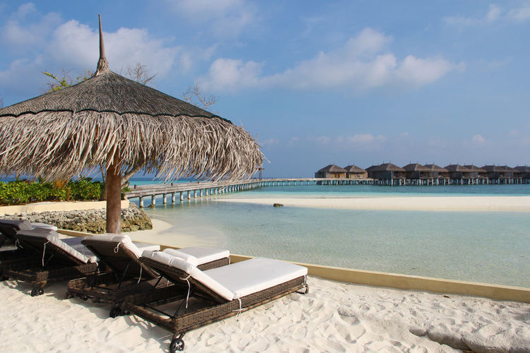 Comfortable Tropical White Sand Beach Sunshine Sunlight Relax Relaxing Maldives Blue Straw Umbrella Deck Umbrella Deck Chair Outdoors Travel Destinations No People Lounge Chair Day Nature Beach Cloud - Sky Sea Sky Water Parasol