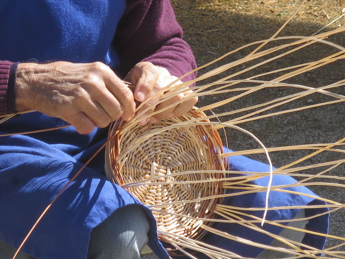 Midsection Of Craftsperson Making Wicker Basket